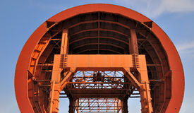 Tunnel working equipment under blue sky. Tunnel working construction machine under blue sky, shown as featured structure, arch shape and orange color Stock Photo