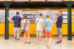 Tunnelbana som skriver in en station av den Budapest tunnelbanan med folk som framme väntar royaltyfria bilder