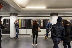 Tunnelbana som skriver in en station av den Budapest tunnelbanan med folk som framme väntar på linje 2 fotografering för bildbyråer