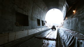 Tunneling. Building site tunnel. Car walks into light in a tunnel stock video footage