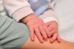 Tunt och långt spikar av ett nyfött behandla som ett barn arkivfoto