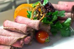 Tunt skivat nötkött med körsbärsröda tomater, grönsallat och apelsiner arkivfoton