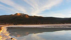 Tunupa火山反射在日出的 01 06 2000年玻利维亚de distance女性湖层放置孤立稀薄在撒拉尔盐旅行家uyuni走的水 免版税图库摄影