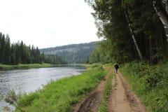 Turístico está en el camino a lo largo del río en las montañas foto de archivo