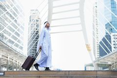 Turbante musulmán y vestido blancos del desgaste de hombre que caminan con equipaje en lugar público y fondo moderno del edificio Fotos de archivo