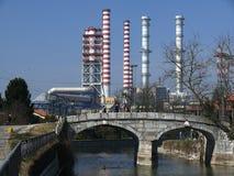 Turbigo, Mil?o, 23/03/2009 Chaminés do central elétrica e uma ponte do canal no primeiro plano fotografia de stock