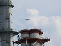 Turbigo, Milaan, 23/03/2009 Vliegtuigvliegen over de schoorstenen van een elektrische centrale stock foto's