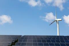 Turbin för vindenergi med några solpaneler för elektricitetsproduktion Fotografering för Bildbyråer