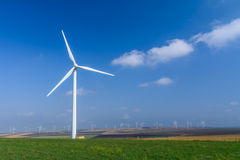 Turbina de viento en el prado en el fondo de cielos Pict colorido Foto de archivo