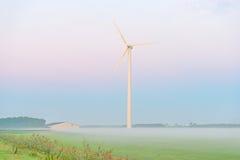 Turbina de viento en un campo en la salida del sol Foto de archivo libre de regalías