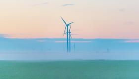 Turbina de viento en un campo en la salida del sol Imágenes de archivo libres de regalías