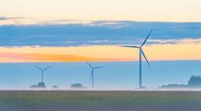 Turbina de viento en un campo en la salida del sol Foto de archivo