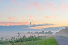 Turbina de viento en un campo en la salida del sol Fotografía de archivo