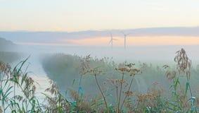 Turbina de viento en un campo en la salida del sol Imagen de archivo libre de regalías