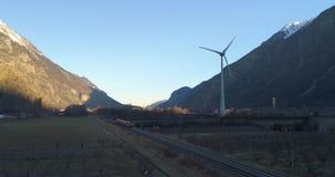 Turbina de viento en un valle del montain con el tren almacen de metraje de vídeo