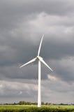 Turbina di vento di luce solare in cieli nuvolosi Fotografia Stock Libera da Diritti