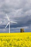 Turbina di vento nel giacimento del seme di ravizzone con la sfuocatura di movimento Fotografie Stock Libere da Diritti
