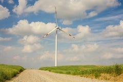 A turbina eólica na paisagem com entrada de automóveis. Foto de Stock Royalty Free