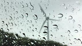 Turbina eólica vista através de um vidro no tempo chuvoso video estoque