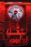 Turbina industrial en luz roja y tubos viejos. Imagen de archivo