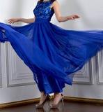 Turbinando in una ragazza ballante della gonna lanuginosa blu in un bello vestito fotografia stock