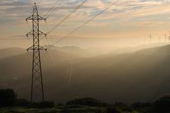 Turbinas de la línea eléctrica y de viento durante puesta del sol Foto de archivo libre de regalías
