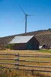 Turbinas de vento atrás de um edifício de exploração agrícola. imagem de stock royalty free