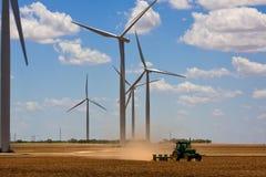 Turbinas de vento e um trator Fotografia de Stock
