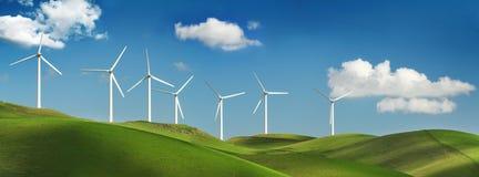 Turbinas de vento em montes verdes Fotografia de Stock Royalty Free