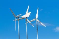 Turbinas de viento blancas produciendo energía alternativa en el cielo azul Foto de archivo