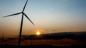 Turbinas de viento del lapso de tiempo sobre un fondo de la puesta del sol almacen de video