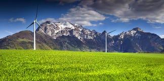 Turbinas de viento eléctrico en el campo del trigo de invierno en las montañas Fotografía de archivo libre de regalías