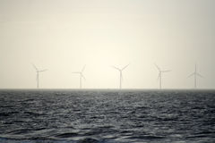 Turbinas de viento en la niebla del mar Fotografía de archivo libre de regalías