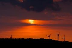 Turbinas de viento en la puesta del sol Imagenes de archivo