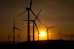 Turbinas de viento en la puesta del sol Fotos de archivo libres de regalías