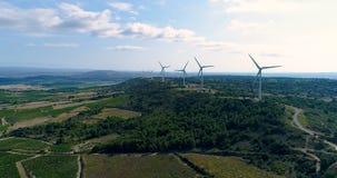 Turbinas de viento en una colina con los campos y las vides almacen de metraje de vídeo