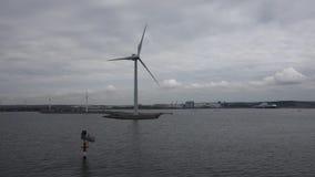 Turbinas de viento a lo largo de la orilla vista del agua