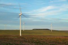 Turbinas de viento que giran en tierra de cultivo abierta Imagen de archivo