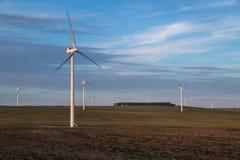 Turbinas de viento que giran en tierra de cultivo abierta Fotos de archivo libres de regalías