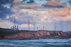 Turbinas de viento que se colocan en el acantilado rugoso sobre el océano en Australia en la puesta del sol Fotografía de archivo