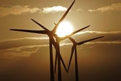 Turbinas de viento silueteadas contra una puesta del sol Fotografía de archivo