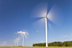 Turbinas de viento verdes de la energía en el campo de girasoles Imagen de archivo libre de regalías