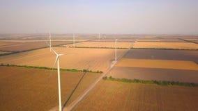 Turbinas de viento y campos agrícolas en un día de verano - producción energética con limpio y la energía renovable - tiro aéreo almacen de metraje de vídeo