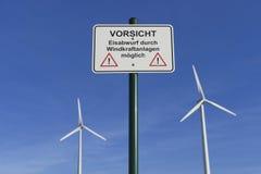 Turbinas de viento y señal de peligro Imágenes de archivo libres de regalías