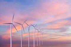 Turbinas dos geradores de vento no mar no por do sol Fotografia de Stock Royalty Free