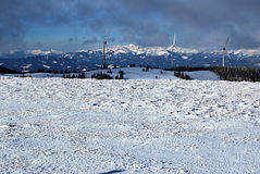 Turbinas eólicas com picos no fundo em cumes do austríaco do inverno Imagem de Stock