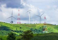 Turbinas eólicas da montanha e torres da energia elétrica Fotos de Stock