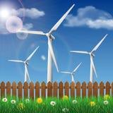 Turbinas eólicas em um campo de grama atrás de uma cerca de madeira Imagens de Stock Royalty Free