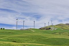 Turbinas eólicas em uma exploração agrícola de vento em um monte foto de stock
