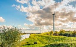 Turbinas eólicas em uma paisagem holandesa com diques e cl de ameaça fotos de stock